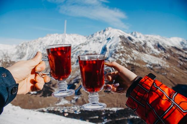 Świąteczne kubki nad górami w rękach zakochanych. wakacje w górach.