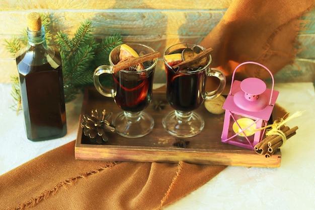 Świąteczne kubki z przyprawami do grzanego wina na drewnianym tle pocztówka koncepcja komfortu w domu