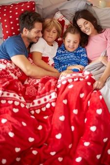 Świąteczne lenistwo rodziny w łóżku