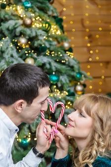 Świąteczne lizaki w rękach mężczyzny i kobiety. selektywne skupienie. wakacje.