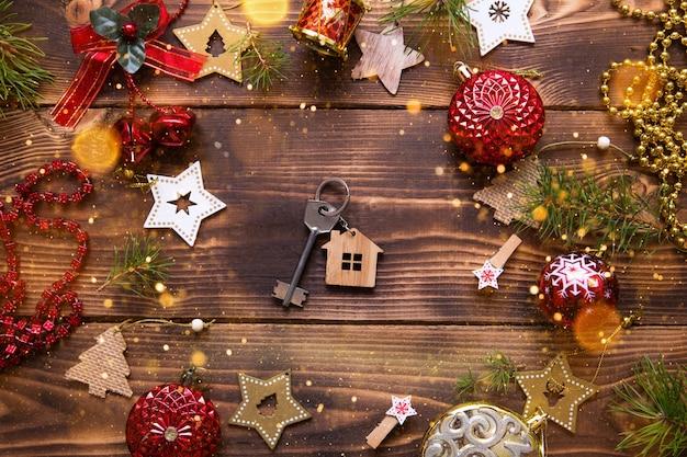 Świąteczne mieszkanie leżało na drewnianym tle z kluczami do nowego domu w centrum z miejscem na notatki