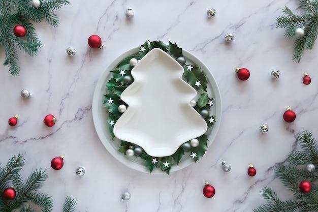 Świąteczne mieszkanie leżało na marmurowym stole, kopia przestrzeń na ceramicznym talerzu. boże narodzenie tło w kolorze zielonym, białym i czerwonym. naturalne gałązki jodły, liście ostrokrzewu i szklane bibeloty.