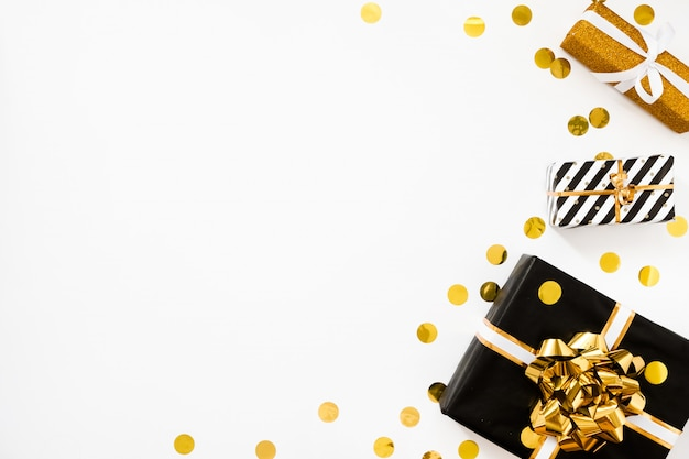 Świąteczne mieszkanie leżało. prezenty świąteczne, czarny i złoty papier pakowy na białym tle ze złotymi konfetti