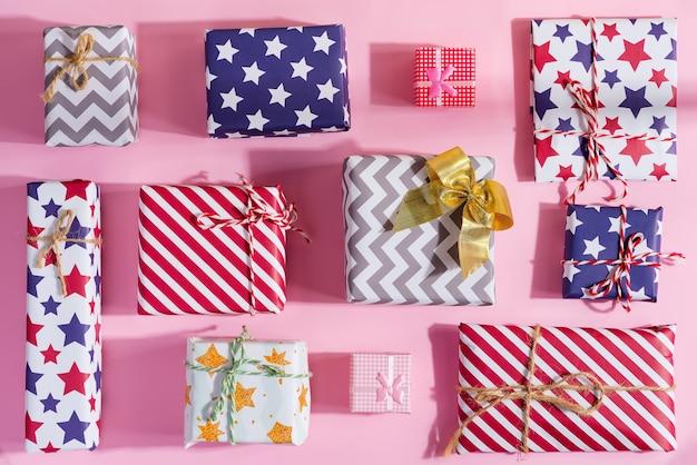 Świąteczne mieszkanie leżało z kolorowymi pudełkami na prezenty z świąteczną dekoracją na pastelowym różu