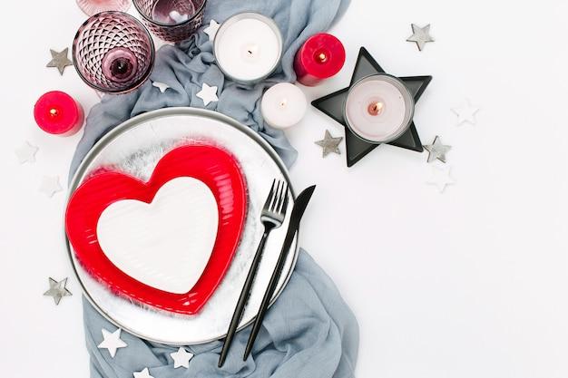 Świąteczne nakrycie stołu. białe i czerwone naczynia w formie serca, szklanki do napojów, świece i sztućce białe tło. walentynki lub koncepcja ślubu
