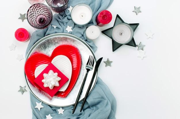 Świąteczne nakrycie stołu. białe i czerwone naczynia w formie serca, szklanki do napojów, świece i sztućce na białym tle. walentynki lub koncepcja ślubu