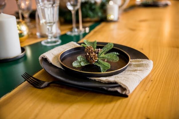 Świąteczne nakrycie stołu. czarna zastawa stołowa i dekoracja z gałęzi jodły. leżał płasko, widok z góry. elegancki sylwestrowy elegancki stół obiadowy z dekoracjami. świąteczny stół do świętowania.