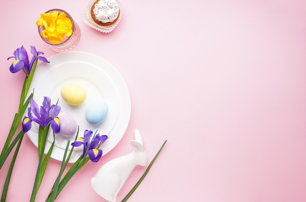 Świąteczne nakrycie stołu i talerze z kolorowymi jajkami na różowo