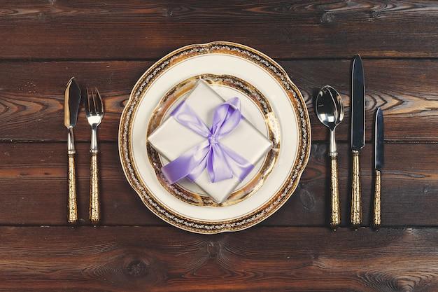 Świąteczne nakrycie stołu na drewnianym stole w kolorach bzu
