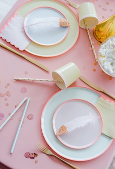 Świąteczne nakrycie stołu na imprezę dla dzieci z tekstylnym różowym obrusem, papierowymi kolorowymi filiżankami, słomkami koktajlowymi. wszystkiego najlepszego dla dziewczynki, dekoracji baby shower.