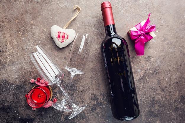 Świąteczne nakrycie stołu na walentynki z butelki, szklanki i pudełko na ciemnym tle kamienia. miejsce na tekst. widok z góry.