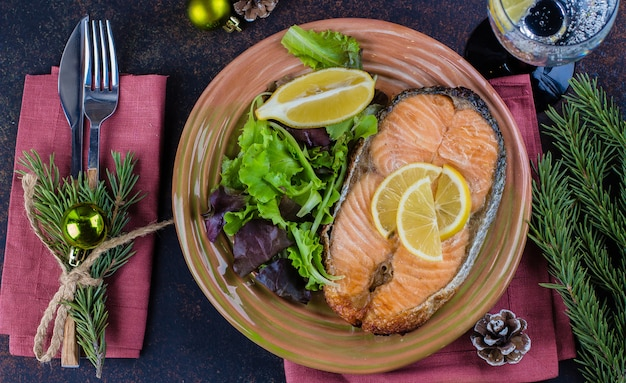 Świąteczne nakrycie stołu. pyszny stek z łososia z grilla na talerzu z cytryną i bukietem surówek na stole z ciemnego kamienia. widok z góry, kopia przestrzeń