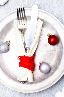 Świąteczne nakrycie stołu. tło wakacje srebrny talerz, nóż i widelec z ozdób choinkowych. widok z góry.