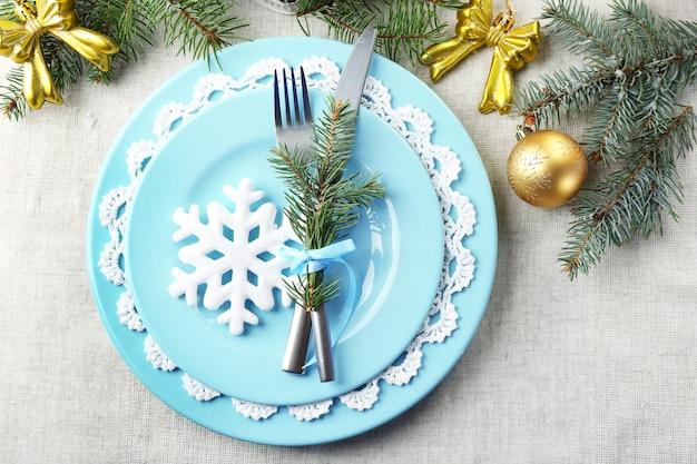 Świąteczne nakrycie stołu w kolorze niebieskim, złotym i białym na szarym tle obrusu