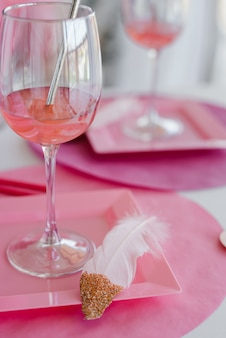 Świąteczne nakrycie stołu w różowych kolorach, talerzach, szklankach. baby shower, urodziny lub impreza dla dziewcząt. ścieśniać