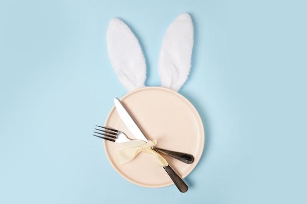 Świąteczne nakrycie stołu wielkanocnego z białymi uszami zajączka wielkanocnego