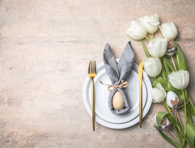 Świąteczne nakrycie stołu wielkanocnego z zajączkiem z jajka na białym talerzu i tulipany.