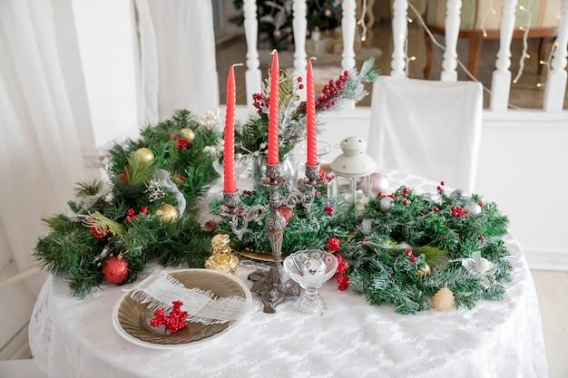 Świąteczne nakrycie stołu wśród dekoracji zimowych i białych świec