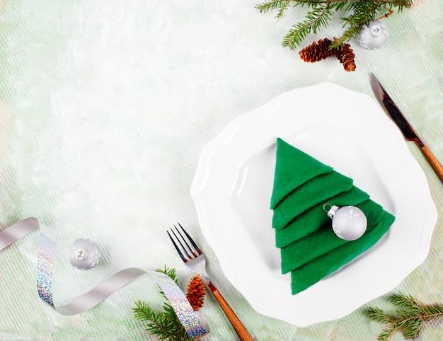 Świąteczne nakrycie stołu z białymi talerzami i zieloną choinką składaną na jasnozieloną serwetkę. widok z góry, lato