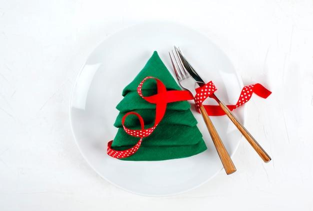Świąteczne nakrycie stołu z białymi talerzami i zieloną choinką, widok z góry serwetka fałd na białym
