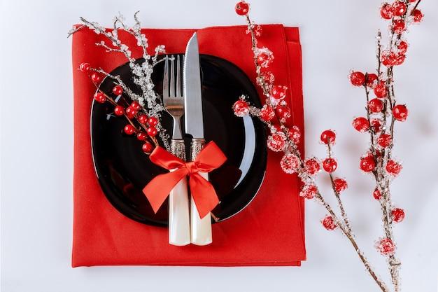Świąteczne nakrycie stołu z czerwoną gałąź jagodową. dekoracja świąteczna.