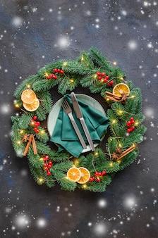 Świąteczne nakrycie stołu z dekoracjami świątecznymi w postaci wieńca świątecznego.