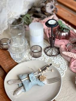 Świąteczne nakrycie stołu z gałązkami suszonych kwiatów i elementami dekoracyjnymi.