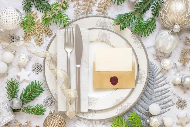 Świąteczne nakrycie stołu z pastelowymi dekoracjami gałęzie jodły pusta karta i zapieczętowana koperta