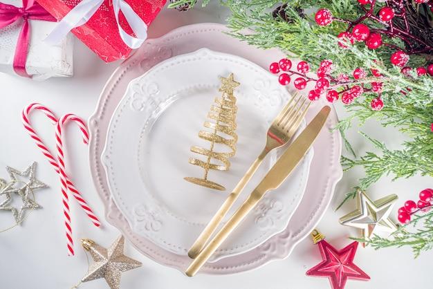 Świąteczne nakrycie stołu z pustymi talerzami, pudełkiem prezentowym i wystrojem bożonarodzeniowym