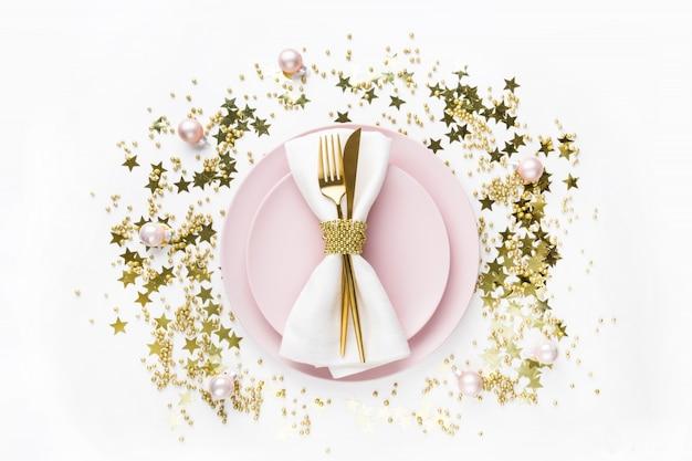 Świąteczne nakrycie stołu z różową zastawą, złote sztućce na białym tle. widok z góry.