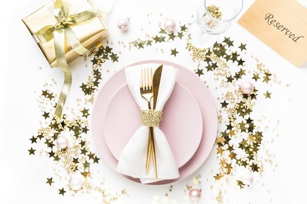 Świąteczne nakrycie stołu z różową zastawą, złote sztućce na białym tle