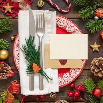 Świąteczne nakrycie stołu z świątecznymi dekoracjami gałęzie jodły pusta karta i zapieczętowana koperta