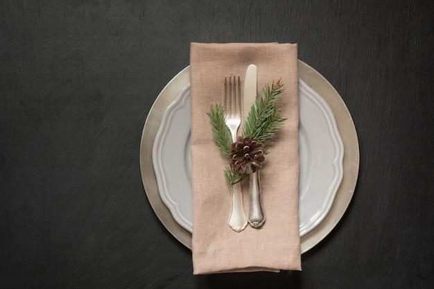 Świąteczne nakrycie stołu ze srebrną zastawą i ciemnym, naturalnie zimozielonym wystrojem.