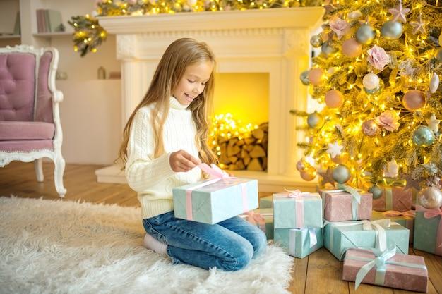 Świąteczne niespodzianki. blondynka śliczna dziewczyna trzyma prezenty i szuka zainteresowanych