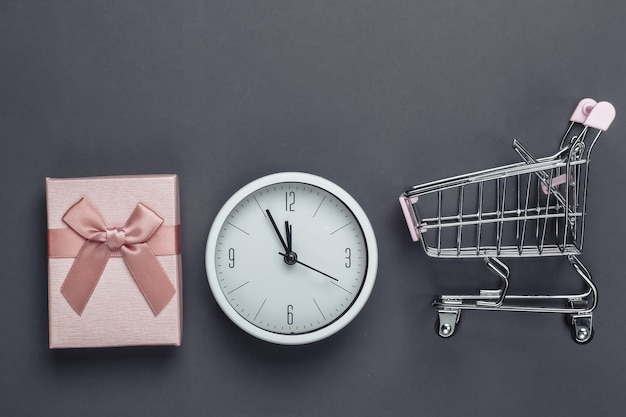 Świąteczne, noworoczne zakupy. mini wózek do supermarketu z pudełkiem na prezent i zegarem na szarej powierzchni. widok z góry