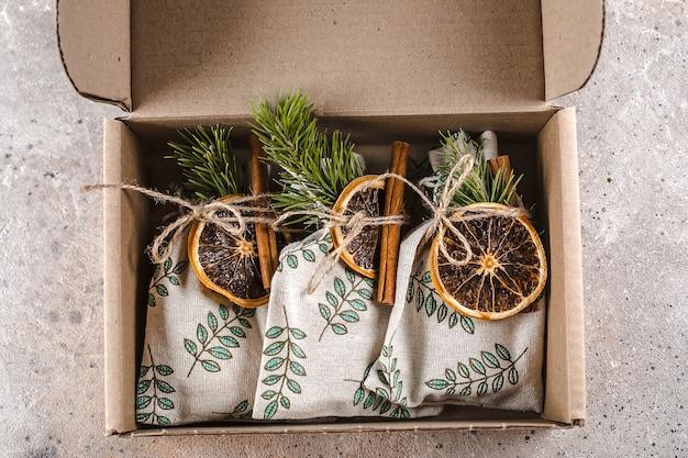 Świąteczne opakowanie tekstylne na prezent w papierowym pudełku. widok z góry, układ płaski