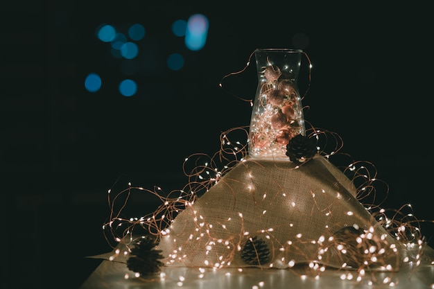 Świąteczne ozdoby. bajki i ozdoby świąteczne w szklanym słoju z ciepłymi światłami świecącymi otoczonymi sznurkiem lampek
