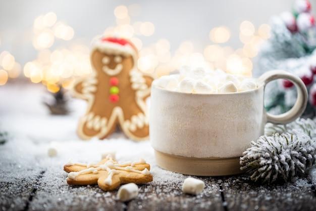 Świąteczne ozdoby na śniegu z filiżanką gorącej czekolady piernikowe gałęzie jodły