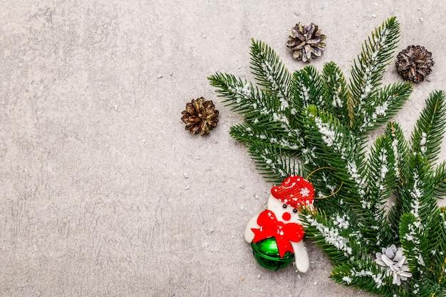 Świąteczne ozdoby. zimozielona gałąź jodły, szyszki, bałwan i sztuczny śnieg.