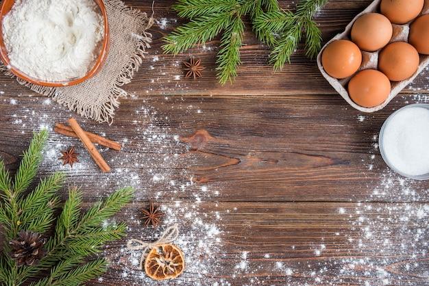 Świąteczne pieczenie ciasteczek imbirowych na ciemnym drewnianym z gałęzi jodłowych.