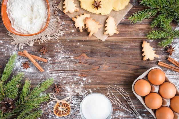 Świąteczne pieczenie ciasteczek imbirowych na ciemnym tle drewnianych z gałęzi jodłowych.