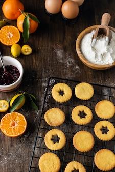 Świąteczne pieczenie, tradycyjne ciasteczka linzer z pomarańczą i dżem jagodowy na drewnianym stole