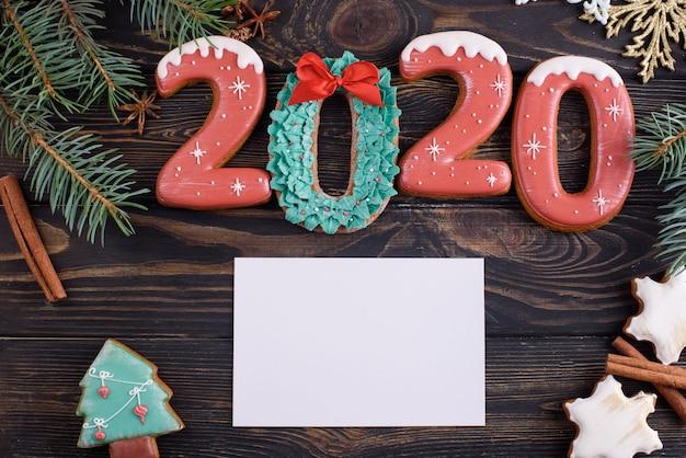 Świąteczne pierniczki numer 2020 na drewnianym stole z aromatycznymi laskami cynamonu