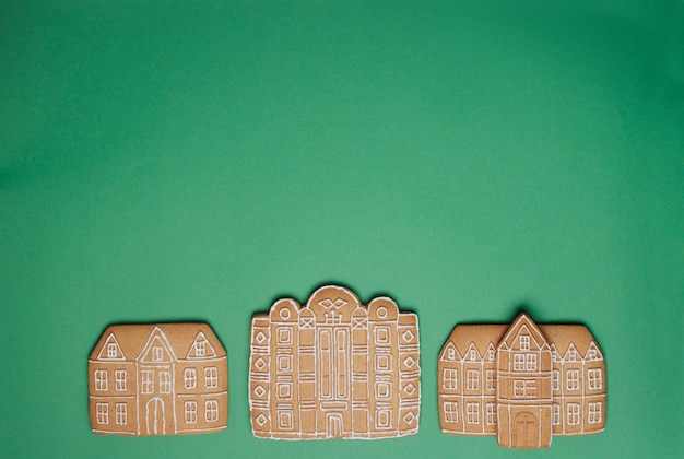 Świąteczne pierniki domy na zielonym tle z pustym miejscem na tekst. widok z góry, płaski układ.
