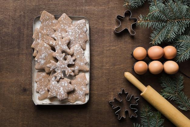 Świąteczne pierniki o różnych kształtach i obramowaniu wiecznie zielonych gałęzi i foremek do ciastek na drewnianej przestrzeni