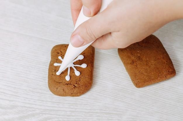 Świąteczne pierniki pomalowane cukrem pudrem. cukierniczka maluje ciasteczka