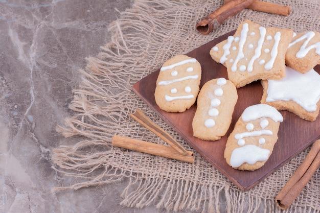 Świąteczne pierniki w kształcie owalu i gwiazdy na drewnianej desce z laskami cynamonu dookoła