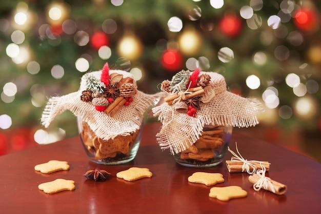 Świąteczne pierniki w szklanym słoju. świąteczne przyprawy i wystrój z bliska. świąteczny tło z bokeh i światłem. nowy rok i kartka świąteczna. magiczna bajka