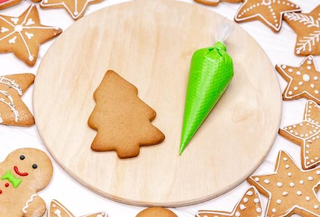 Świąteczne pierniki z dekoracjami na drewnianej desce do krojenia. robienie ciasteczek świątecznych w domu