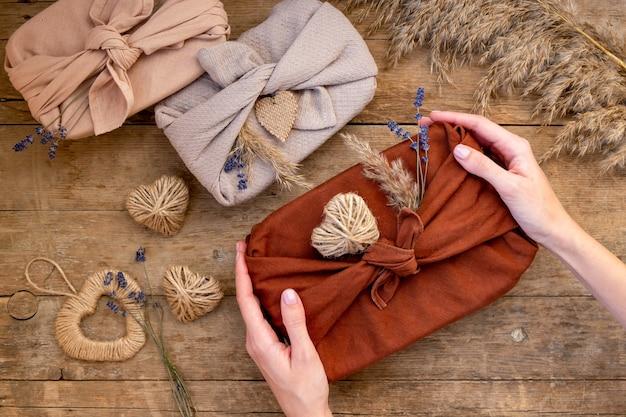 Świąteczne płasko prezentów zapakowanych w stylu furoshiki na drewnianym tle. zero waste koncepcja i makieta na walentynki. z lawendą, jutowymi sercami i trawą pampasową